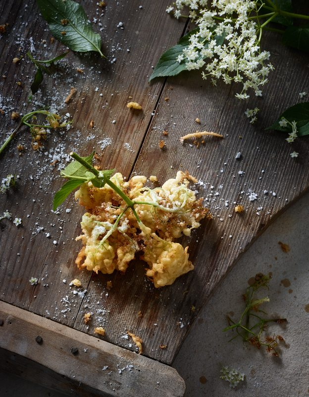 dark food photography of deep-fried Elderbossom on weathered Wood blossoms leafs