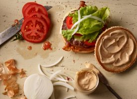 building the cheeseburger with all the ingredients onions tomatos sauce fast food photography C