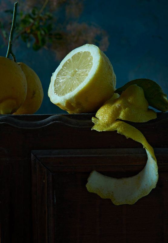 cut lemon on wooden table with pieces of the skin. desserts preparation
