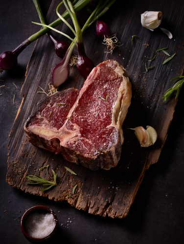 rare t-bone steak dry aged steak with salt garlic and spring onions on a wooden tablet dark food photography