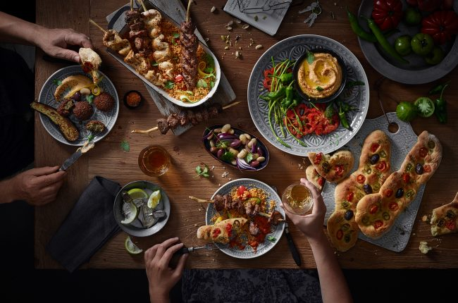 food photography of a big wooden table with allot of dishes mediterranian food hummus meat sauces wine diner