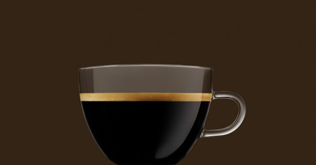 black Coffee in a glass cup with crema brown background
