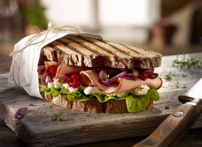 sandwich farmhouse rye bread with leberkaes salad cranberries horseradich on old weathered wooden board old knife alpine hut food styling