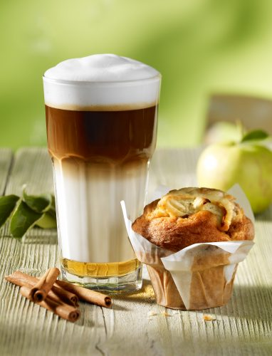 Mc Cafe coffee latte Macciato with apple cinnemon muffin green background weathered green wood table