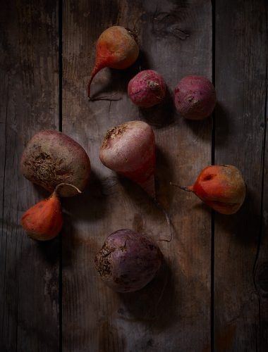 eight beetroot in different colors on washed-out wood underground