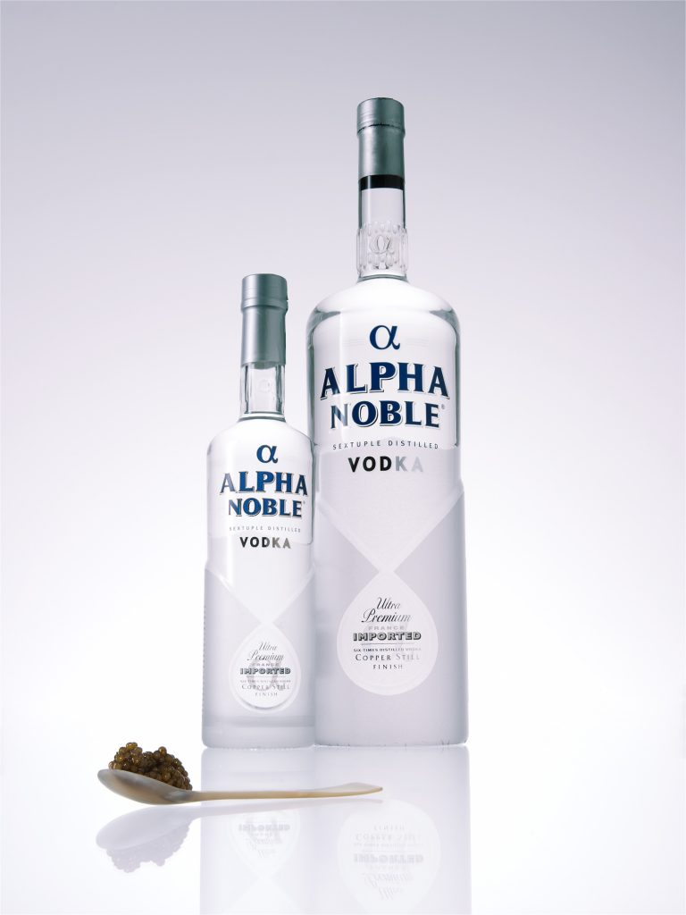 two Vodka bottles with caviar on a horn spoon gradient backdrop