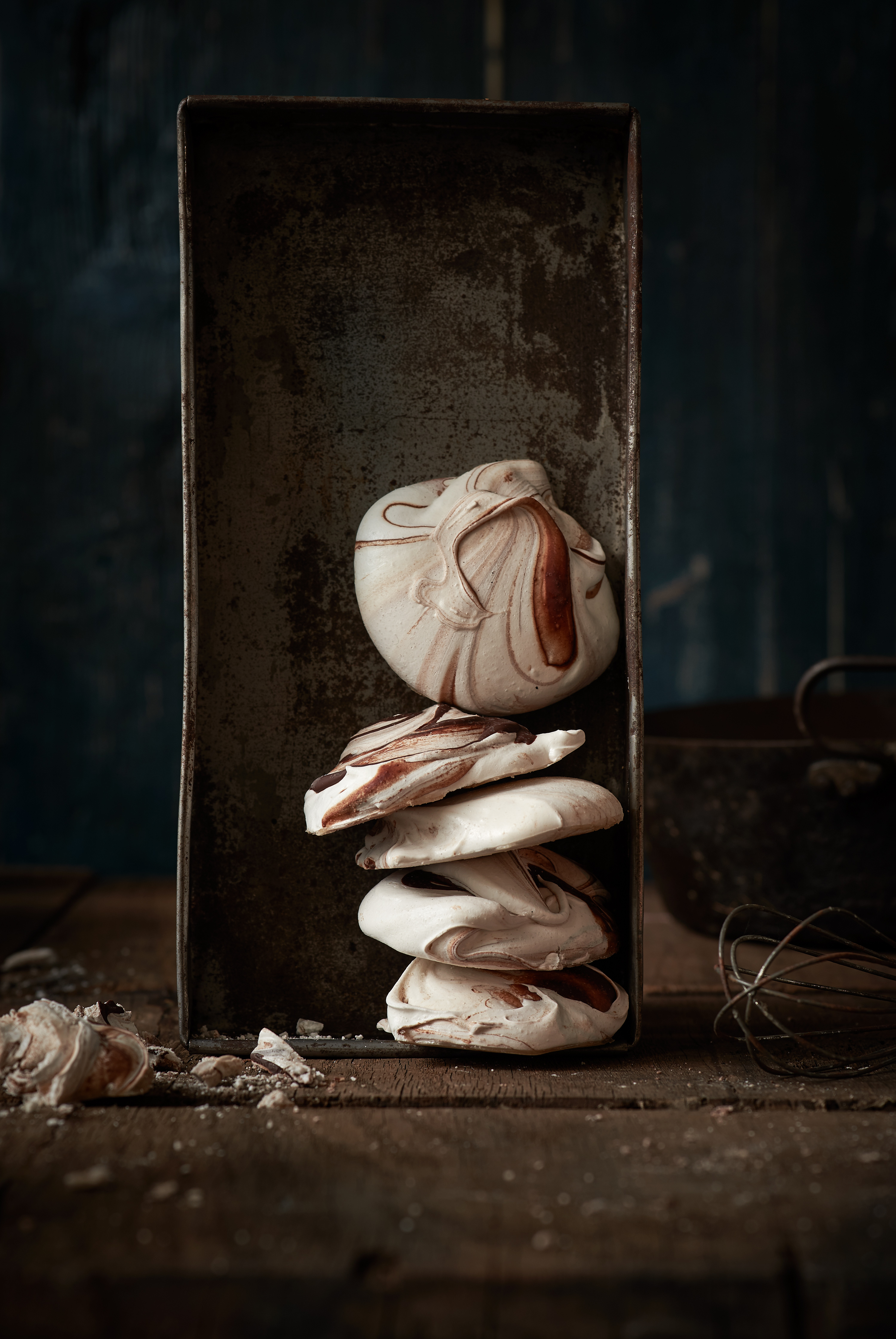 ein stapel schokoladen baiser liegt in einer alten blechdose, daneben liegt ein alter rührbesen, als Untergrund sieht man einen alten Holztisch, der Hintergrund ist blau verblasst