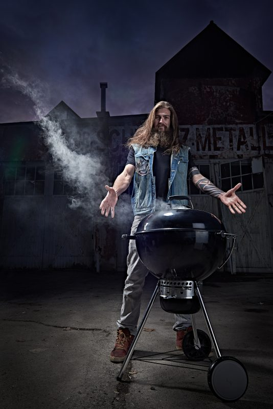 man with arms spread stands behind a barbecue, grilling dinner in front of a industrial location outside shooting