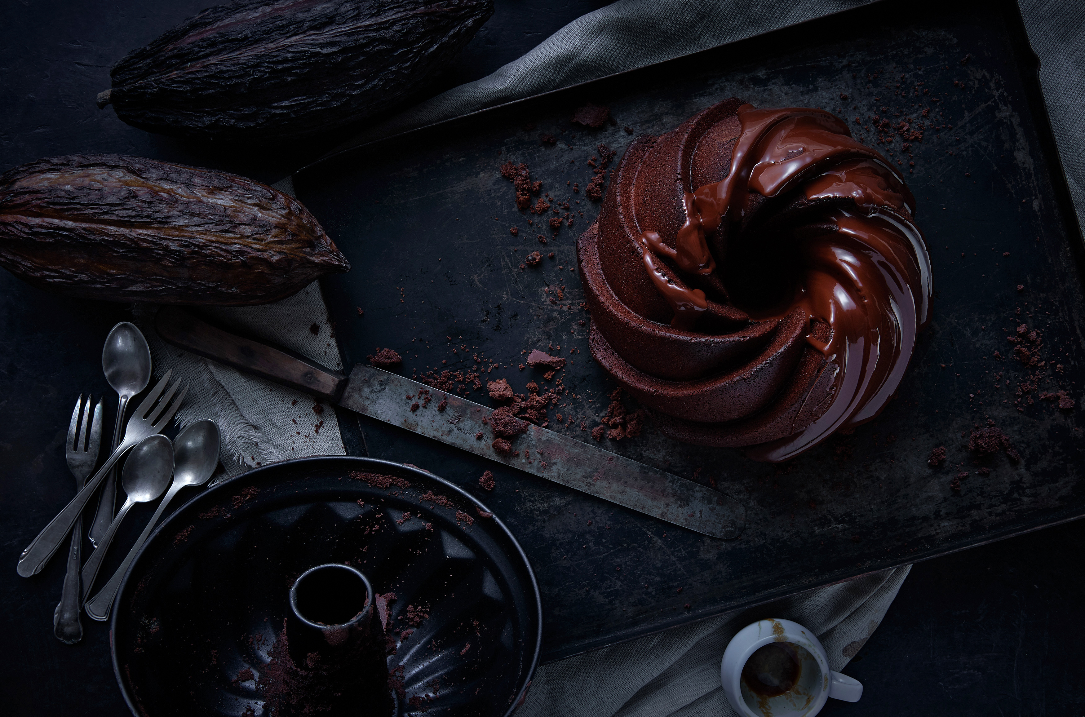 A Chocolate Cake is shot over head a knife cacoa beans and a cake tin are beside dark food photography munich