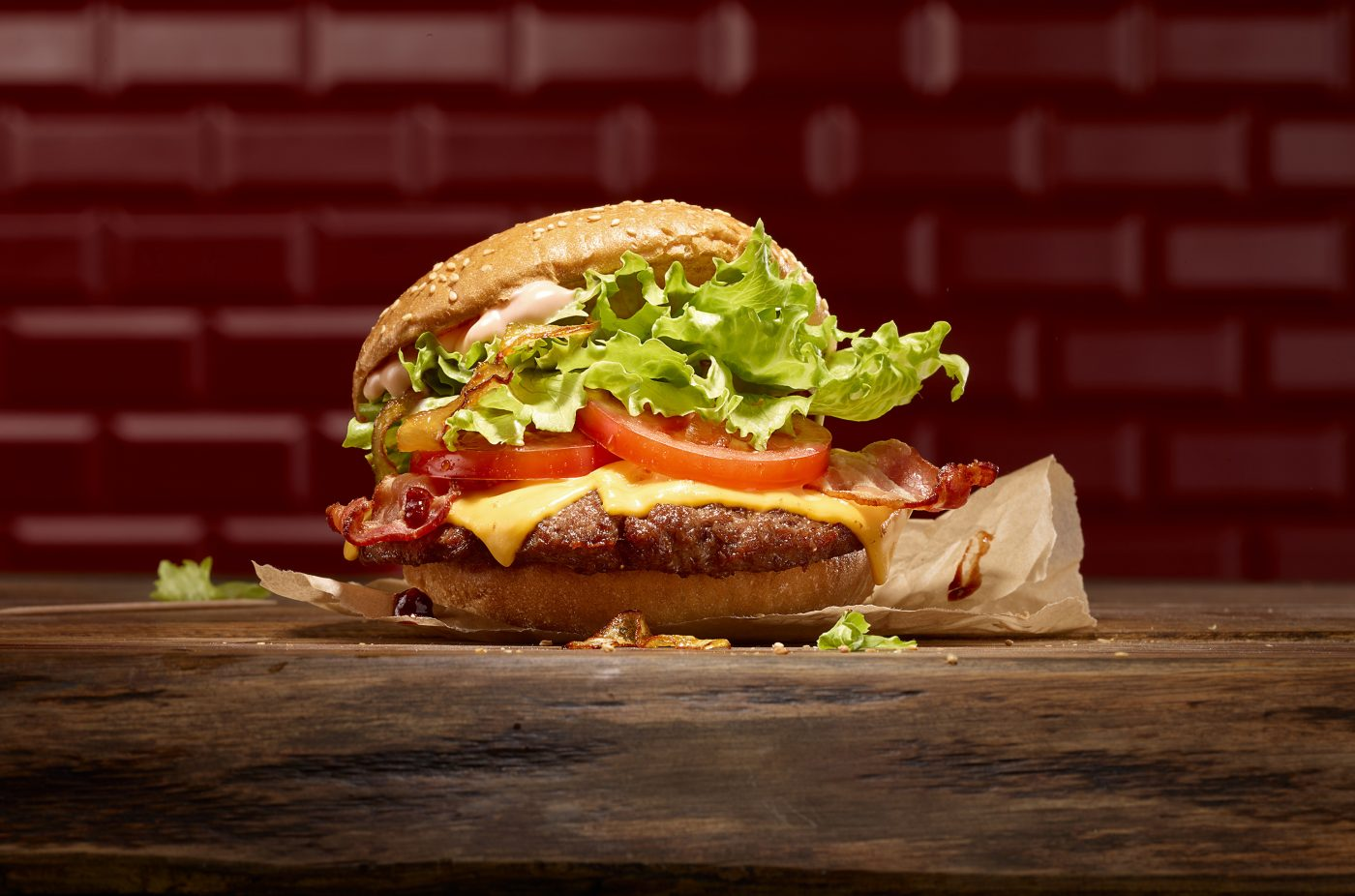 a yummy burger with cheese tomatos salad aud sauce is on a old nice wood table. dark red tiles are in the background