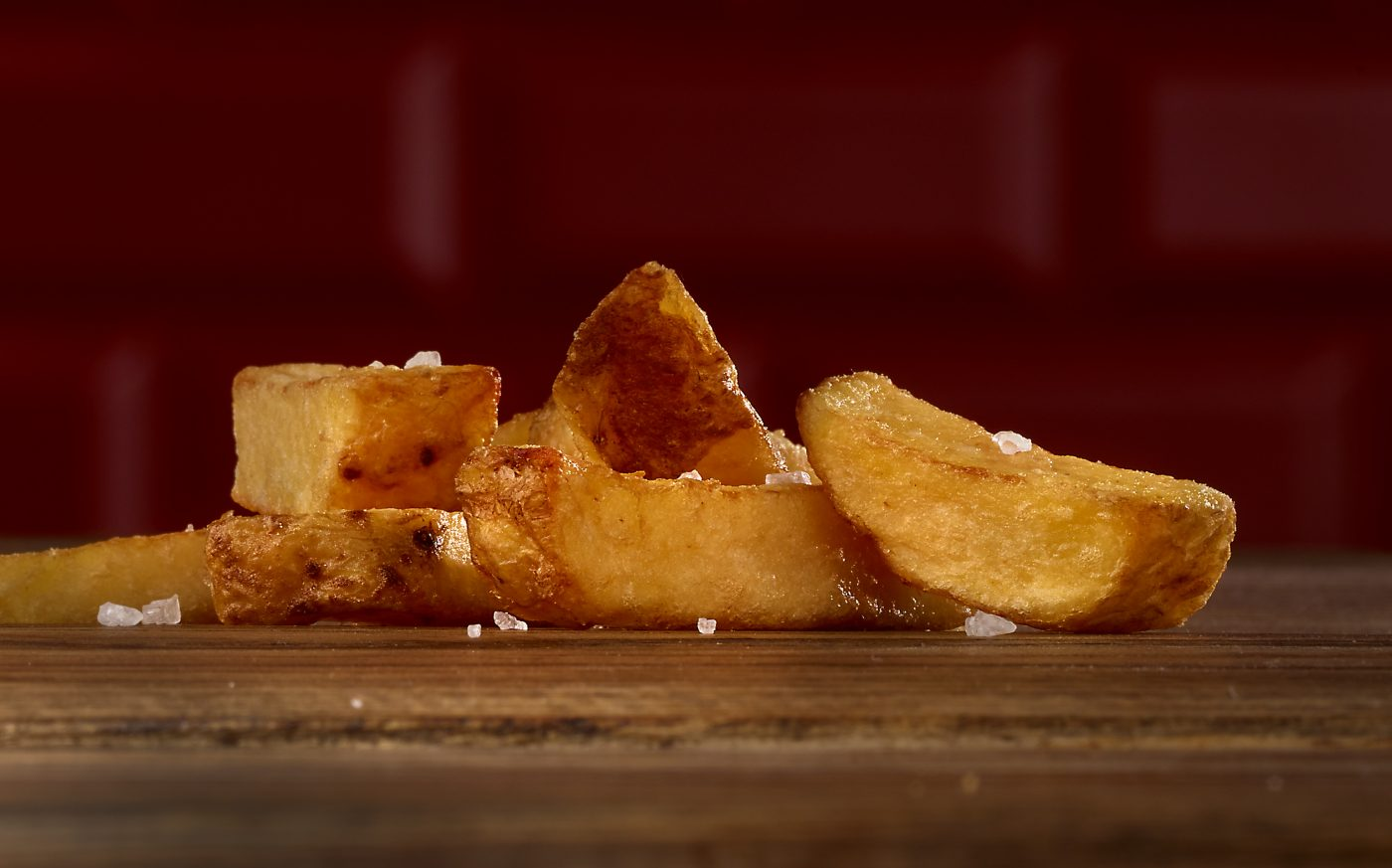yummy potato wedges burger is on a old nice wood table. dark red tiles are in the background