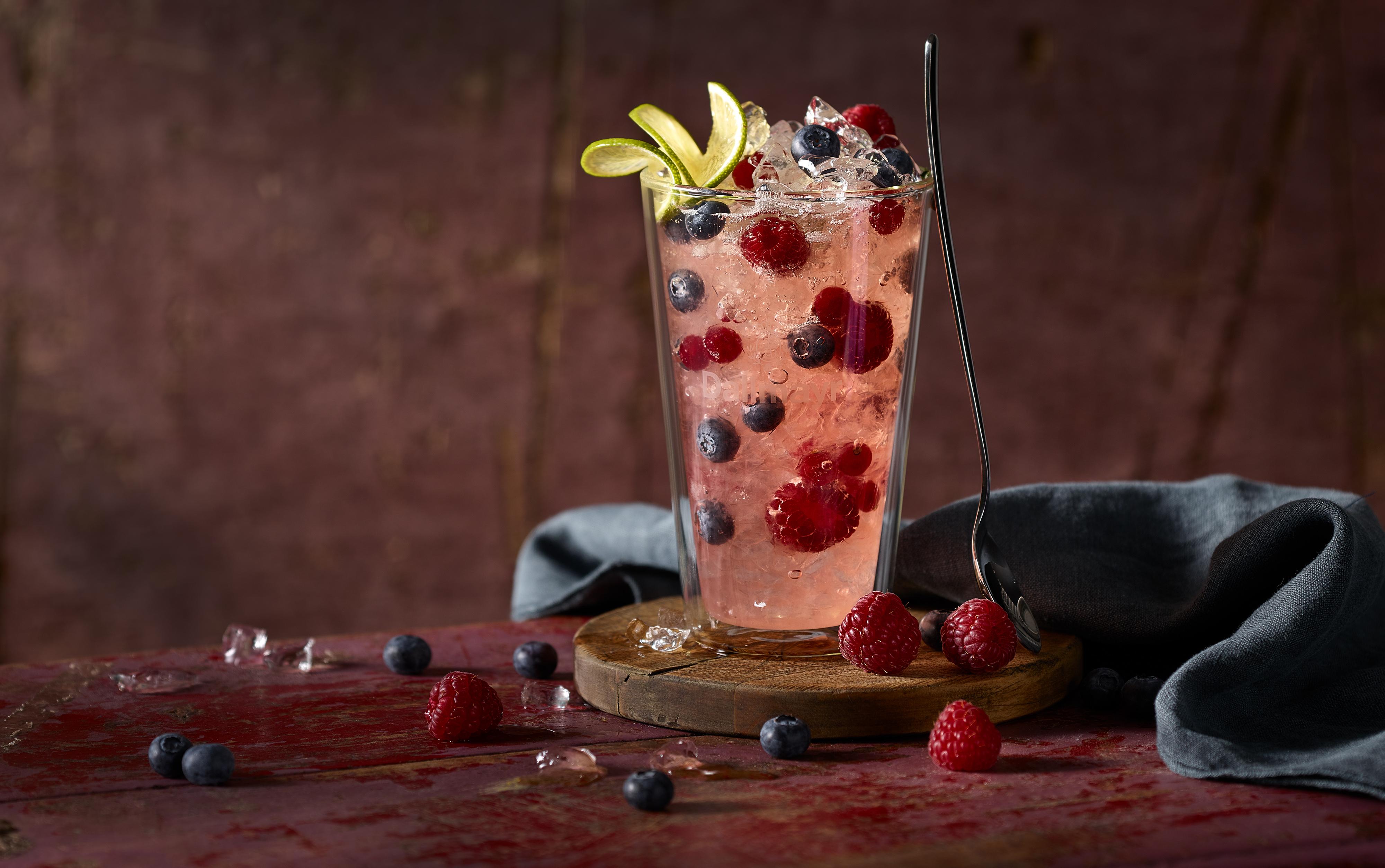 Tee Wild Berry ist im Glas mit Eiswürfeln Himbeeren Blaubeeren. Es ist ein leckes Cocktail Rezept. Hintergrund und Untergrund sind stylisch wie bei Instagram es liegt noch eine Serviette im Hintergrund