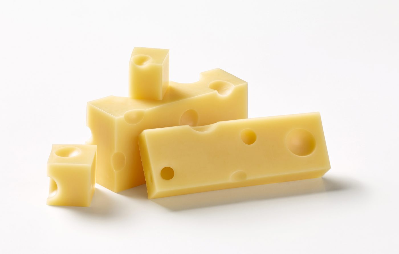 cut pieces of emmental cheese lie on top of each other as a group