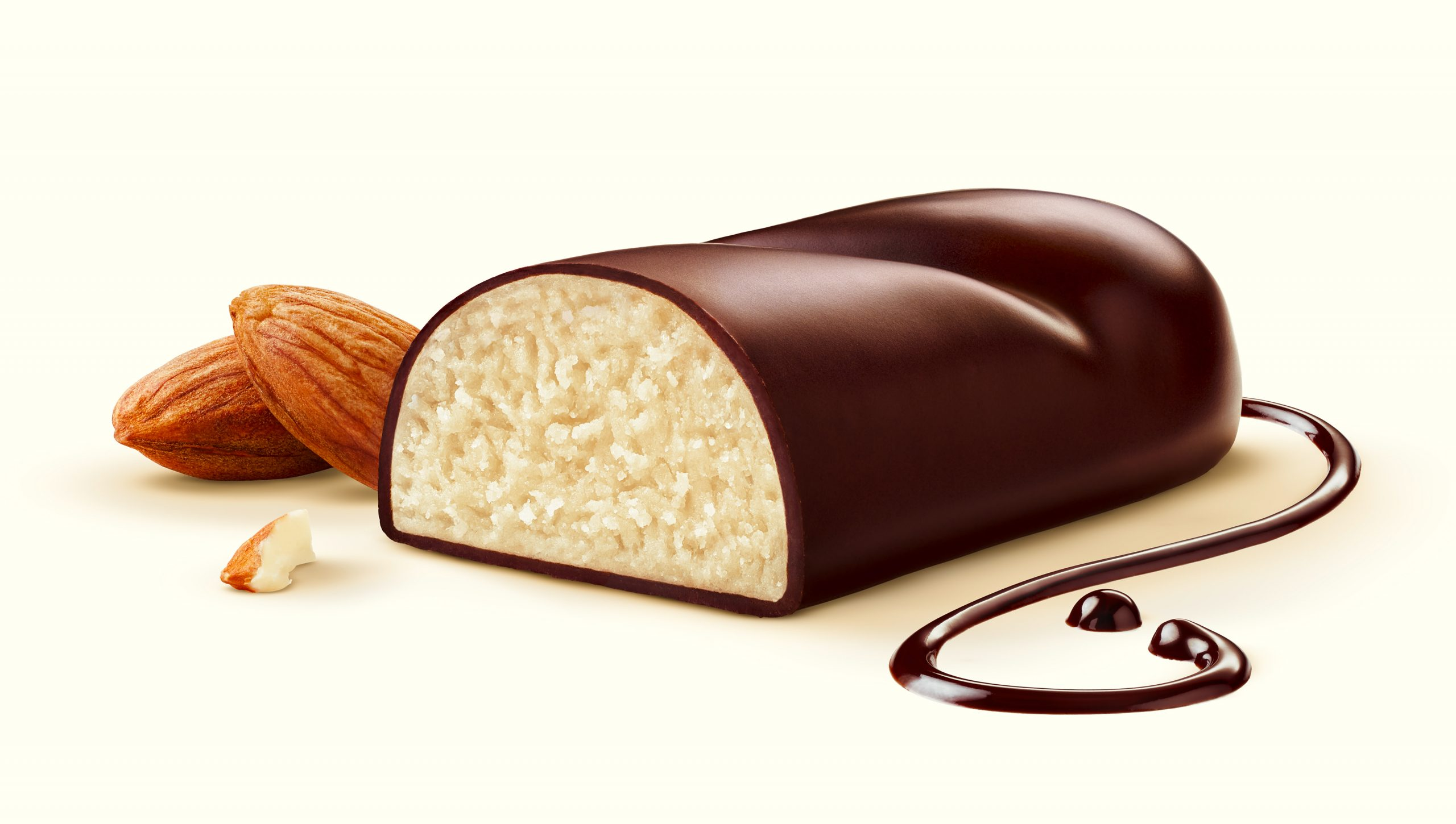 A confectionery marzipan bread is covered with chocolate, on the beige background are fine chocolate streaks.