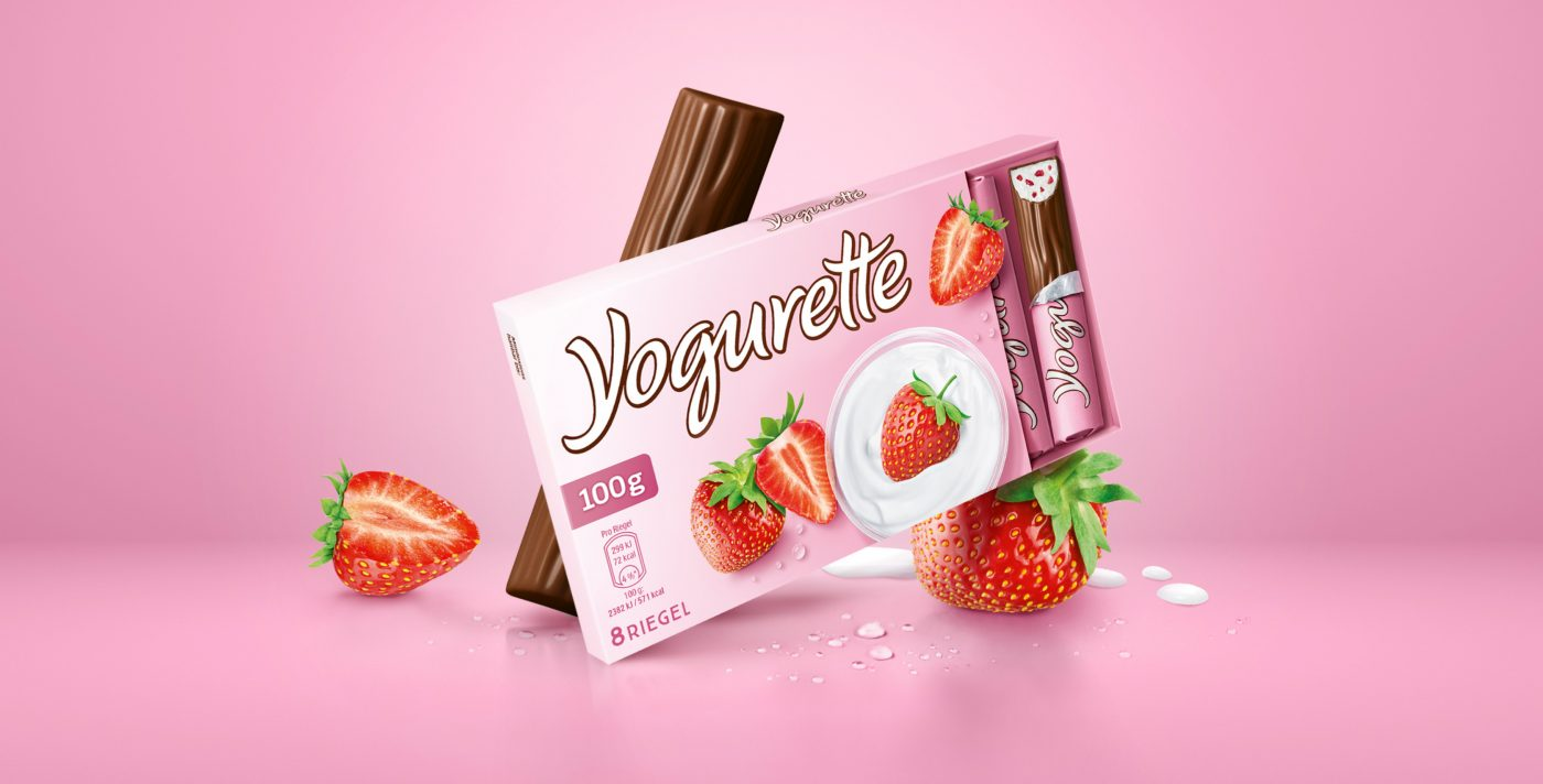 Packaging relaunch Yogurette, a package stands in a virtual pink room with strawberries, chocolate bars and milk drops