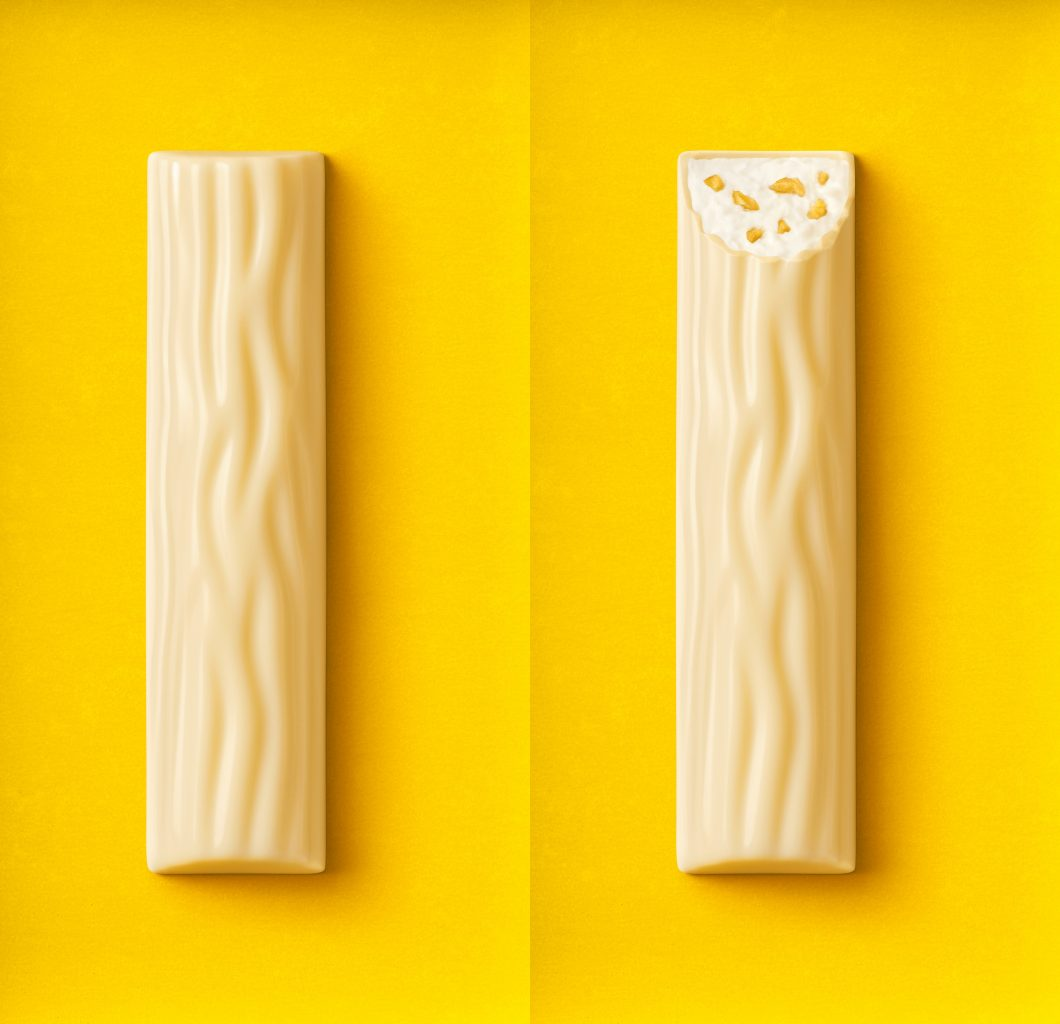 Packaging relaunch for the Yoguretten packaging. A bitten white chocolate bar and an unbitten white chocolate bar passion fruit lie on a yellow background
