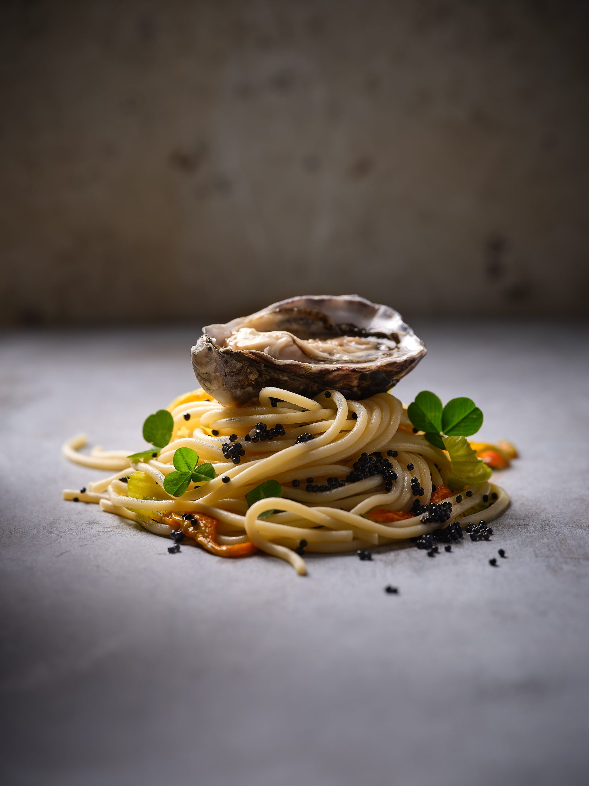 a nest of spaghetti pasta are garnished on top with an oyster